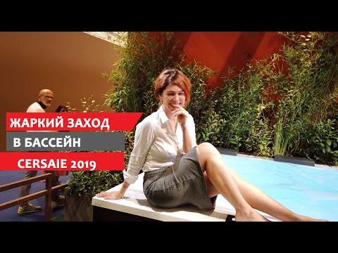Elegante Dame steigt mit Rock und Bluse in eine wassergefüllte Designerbadewanne